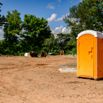 Royalty-free stock photo ID: 1774819424 Porta Potty on an active construction site with earth moving equipment in the background